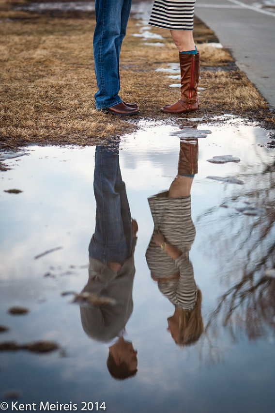 A couples pregnancy portrait in a water reflection